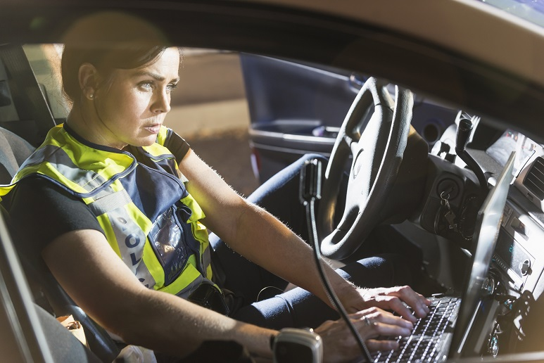 A female police officer sitting in her police car, using the computer. It is nighttime and the emergency lights on her vehicle are flashing.