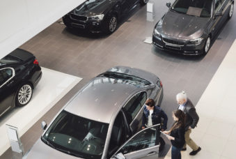 High angle view of saleswoman explaining to customers at car showroom
