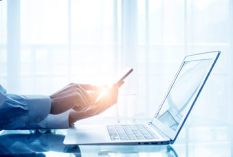 Businessman using mobile phone and laptop in office