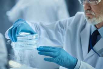 Close-up of a Medical Research Scientist Holds Cold Petri Dish with Samples. He Works in a Busy Modern Laboratory Center.