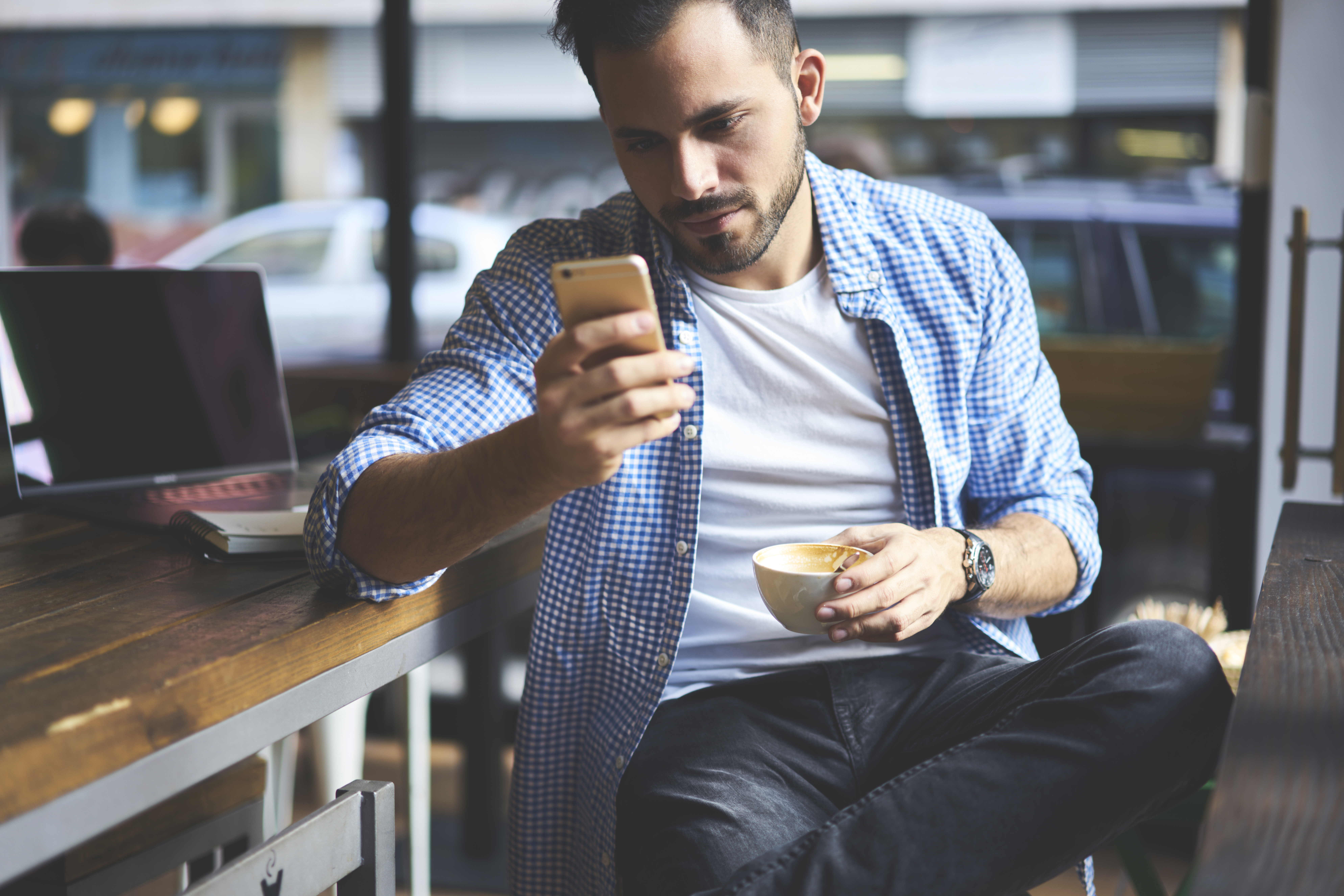 Concentrated casually dressed male freelancer checking email box waiting for transaction using online banking service, serious hipster guy installing application on smartphone during coffee break