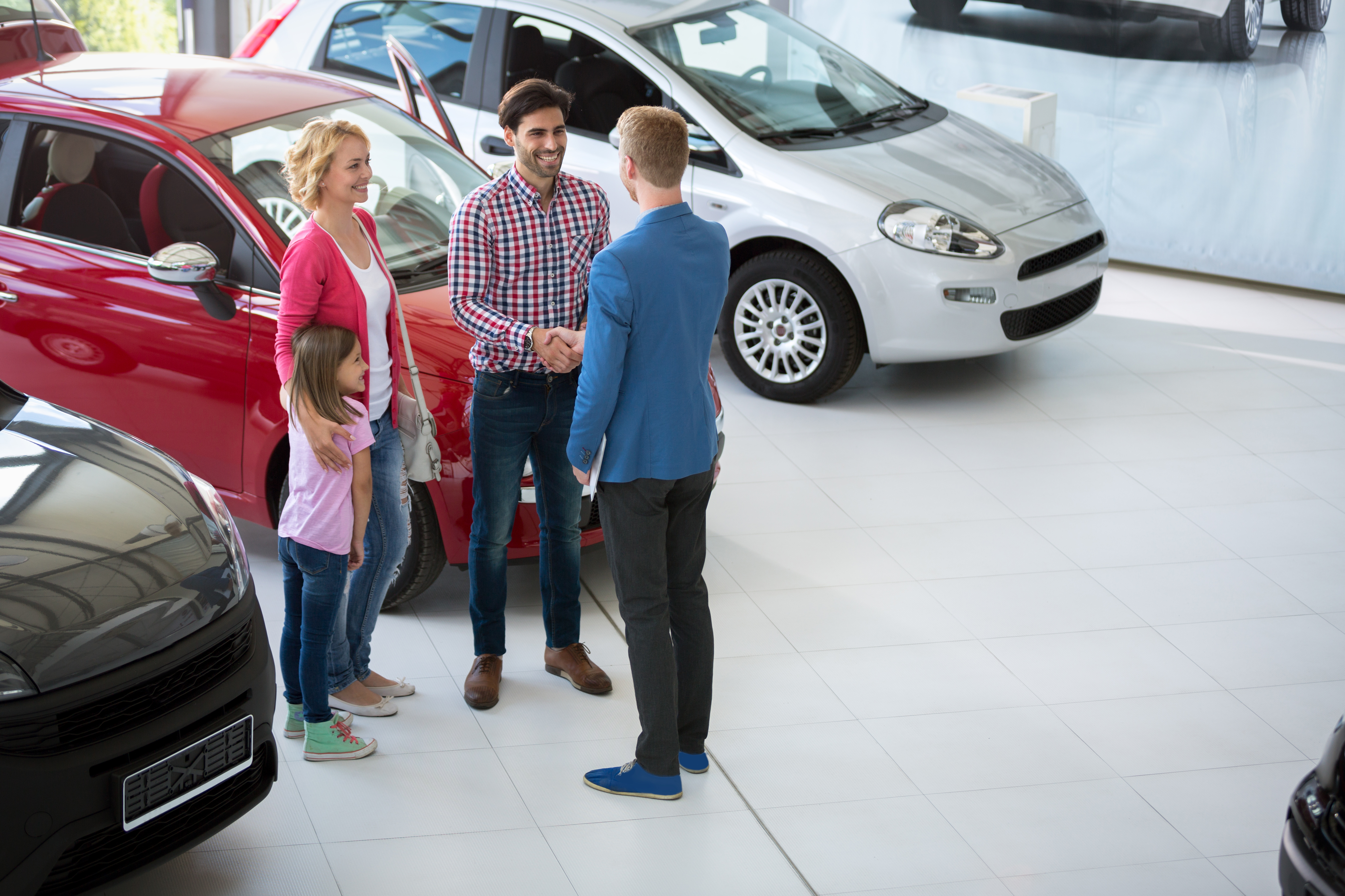 car agent handshake with his daddy and congratulate the family on buying car