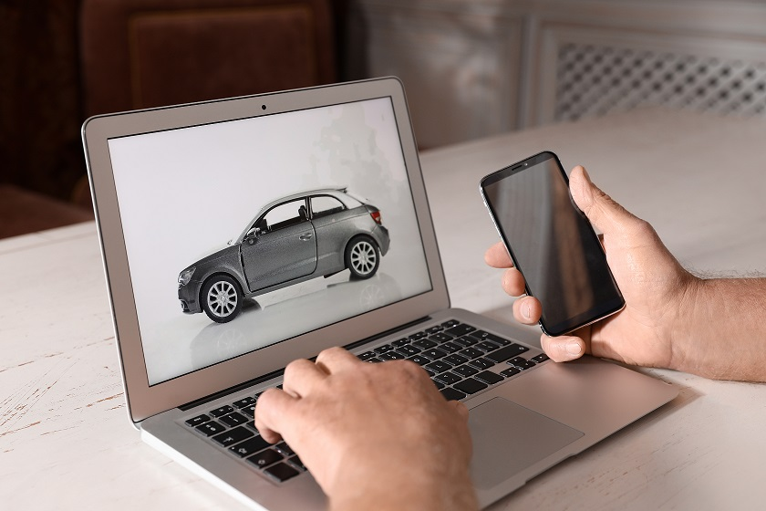 Man using laptop and phone to buy car at wooden table indoors, closeup